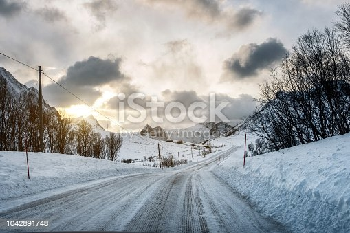 1066508460 istock photo Dirty snow road with sunlight on mountains 1042891748