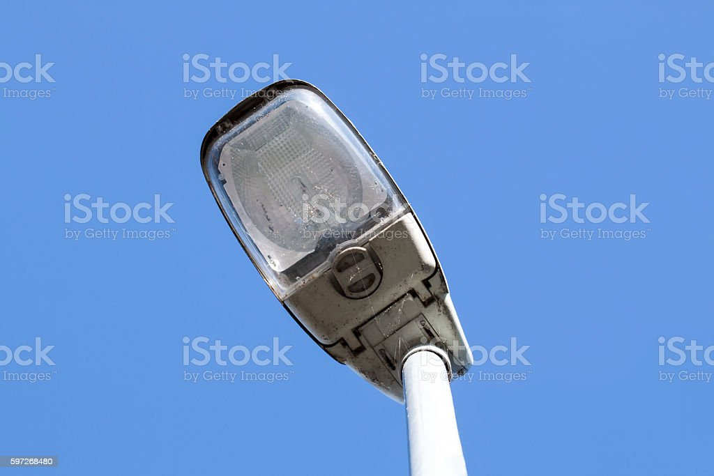 Dirty street lamp in front of a bright blue sky Lizenzfreies stock-foto
