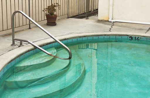 Swimming pool is old and dirty.