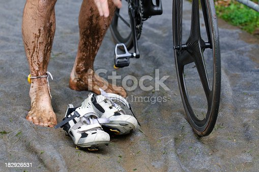 986840244 istock photo Dirty Triathlete in transition zone with timechip 182926531