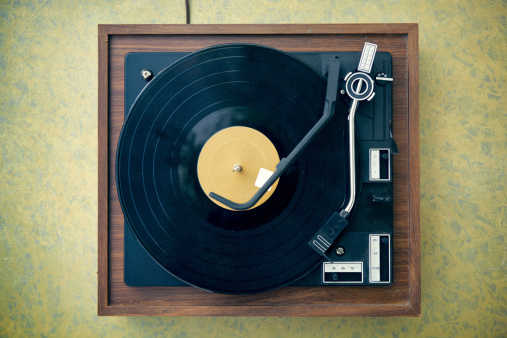 A dusty, dirty, vintage  wood and plastic record player from high angle view (directly above)), with retro formica 1960's table.  Copy space on table and record; horizontal