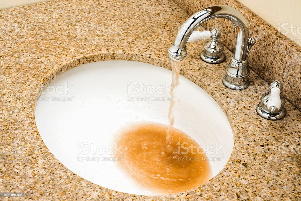 Dirty water pouring out of Vanity faucet into sink bowl stock photo