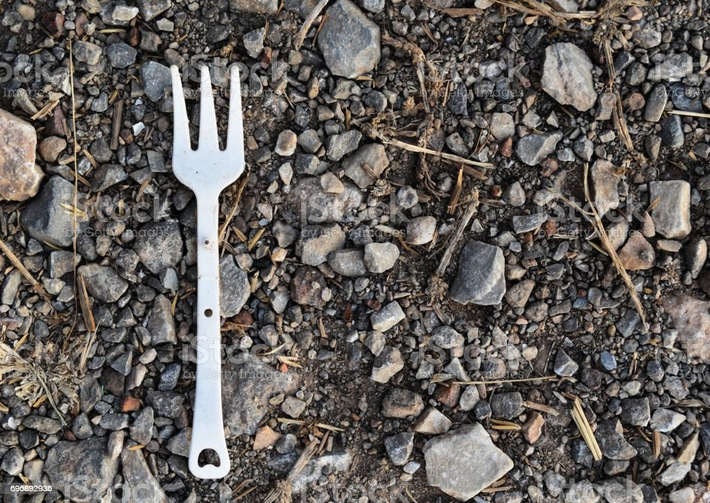 dirty white plastic fork on dirty rough ground stock photo
