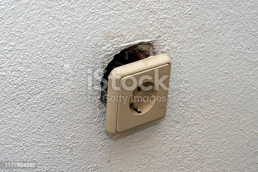 A dirty white socket fell out of the wall and hangs on wires. Repair in the house of old Euro sockets.