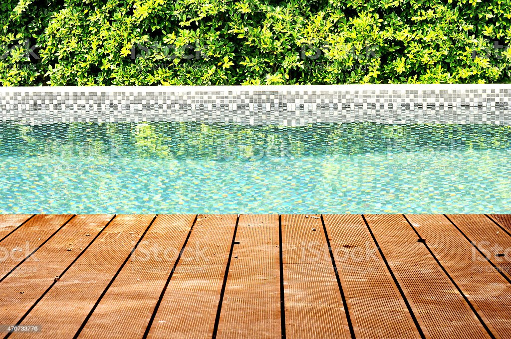 Dirty wooden ground with swimming pool and tree fence stock photo