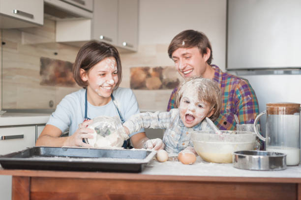dirty young family cooking with flour together at kitchen stock photo