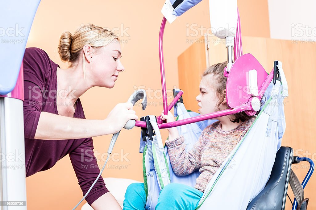 Disability a disabled child being lifted into a wheelchair stock photo