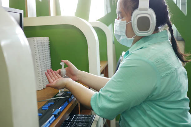 Disability blind person with headphone wearing face mask applying alcohol gel hand sanitizer on hands before using computer with braille display amid Coronavirus (COVID-19) pandemic. Disability blind person with headphone wearing face mask applying alcohol gel hand sanitizer on hands before using computer with braille display amid Coronavirus (COVID-19) pandemic. amid stock pictures, royalty-free photos & images