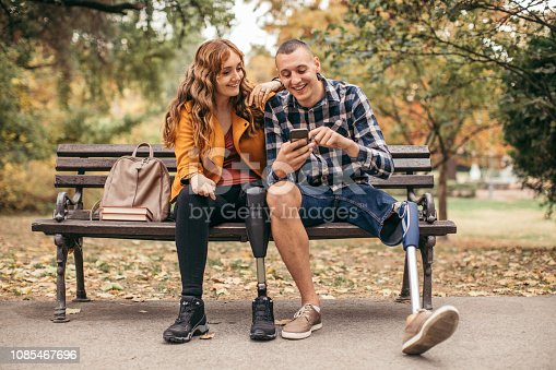 Man and woman, friends sitting in park, they have prosthetic legs, using smart phone.