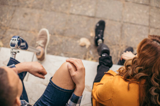 Disability couple sitting together on steps stock photo