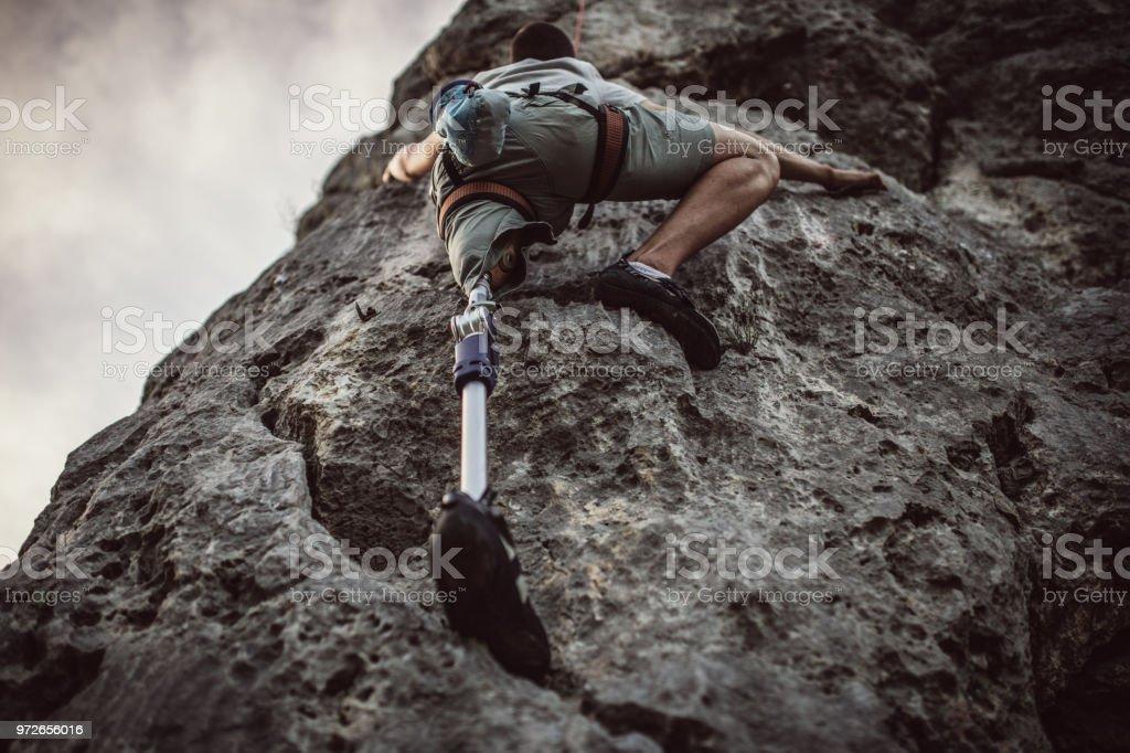 Disability guy climbing stock photo