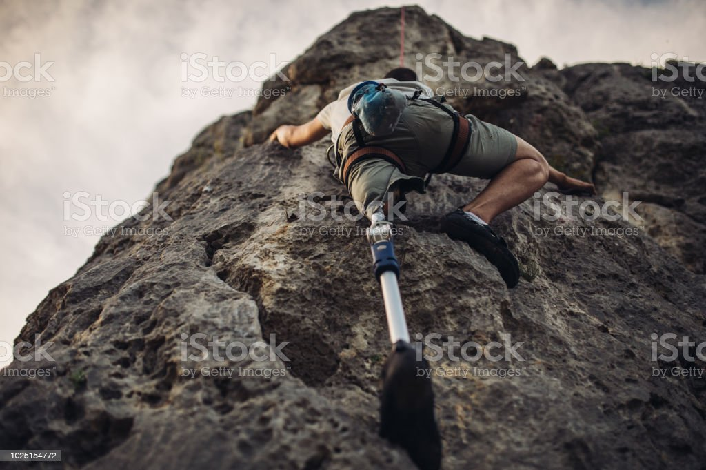 One man, disability young man with prosthetic leg free climbing on a...