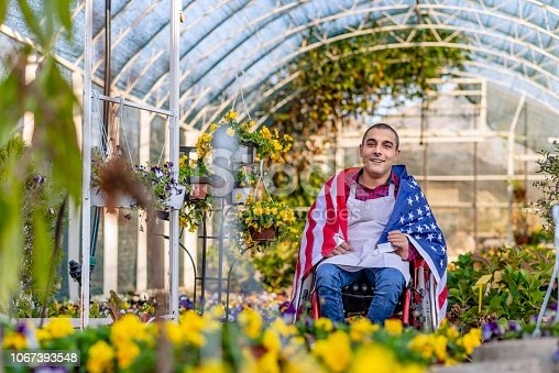 Photo of young happy Disabled man, looking at camera with smile, sitting in wheelchair with flag of USA on the shoulders, working in his greenhouse during the day
