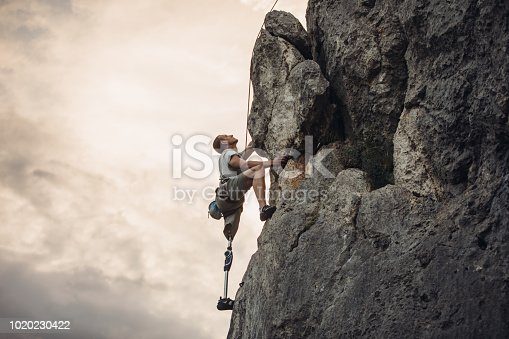 One man, disability young man with prosthetic leg free climbing on a rock in nature..