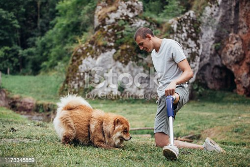 One man, disability young man with prosthetic leg his dog best friend relaxing together in nature.