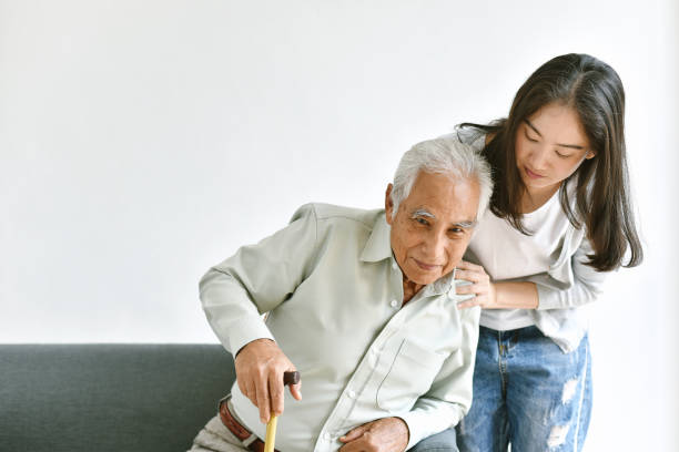 Disable and injury senior asian man try to stand up with walking cane, Knee pain and joint disease in old man, Elderly health problems and insurance concept. stock photo