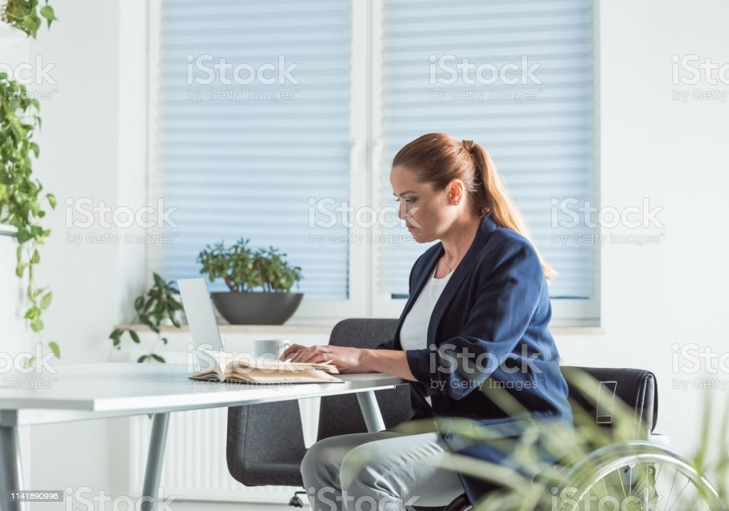 Disable businesswoman reading book at desk Disable businesswoman reading book at desk. Female professional is sitting on wheelchair in office. She is in businesswear. 40-44 Years Stock Photo
