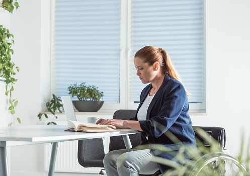 Disable Businesswoman Reading Book At Desk Stock Photo - Download Image Now