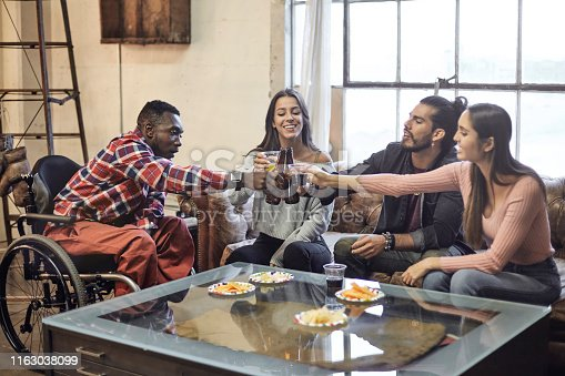 istock Disabled African-American Man Toasting with Hispanic Friends 1163038099