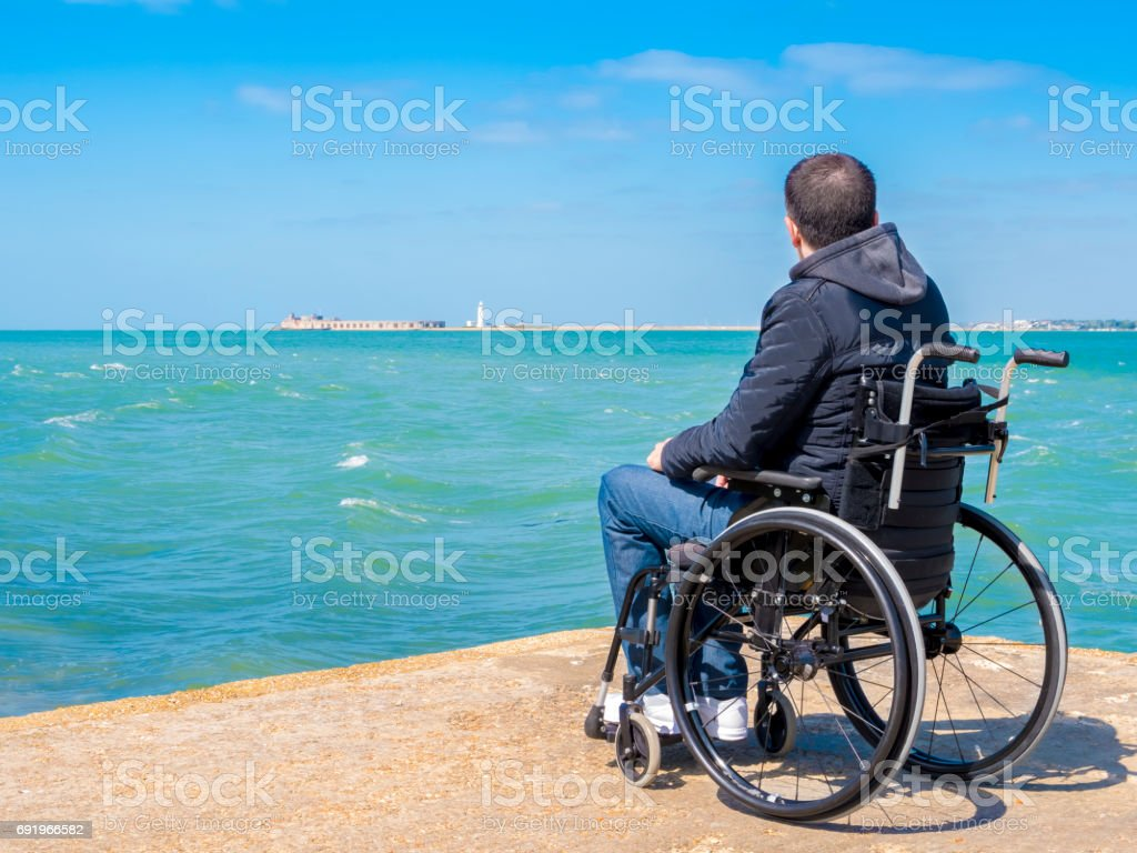 Disabled alone young man sitting in a wheelchair stock photo