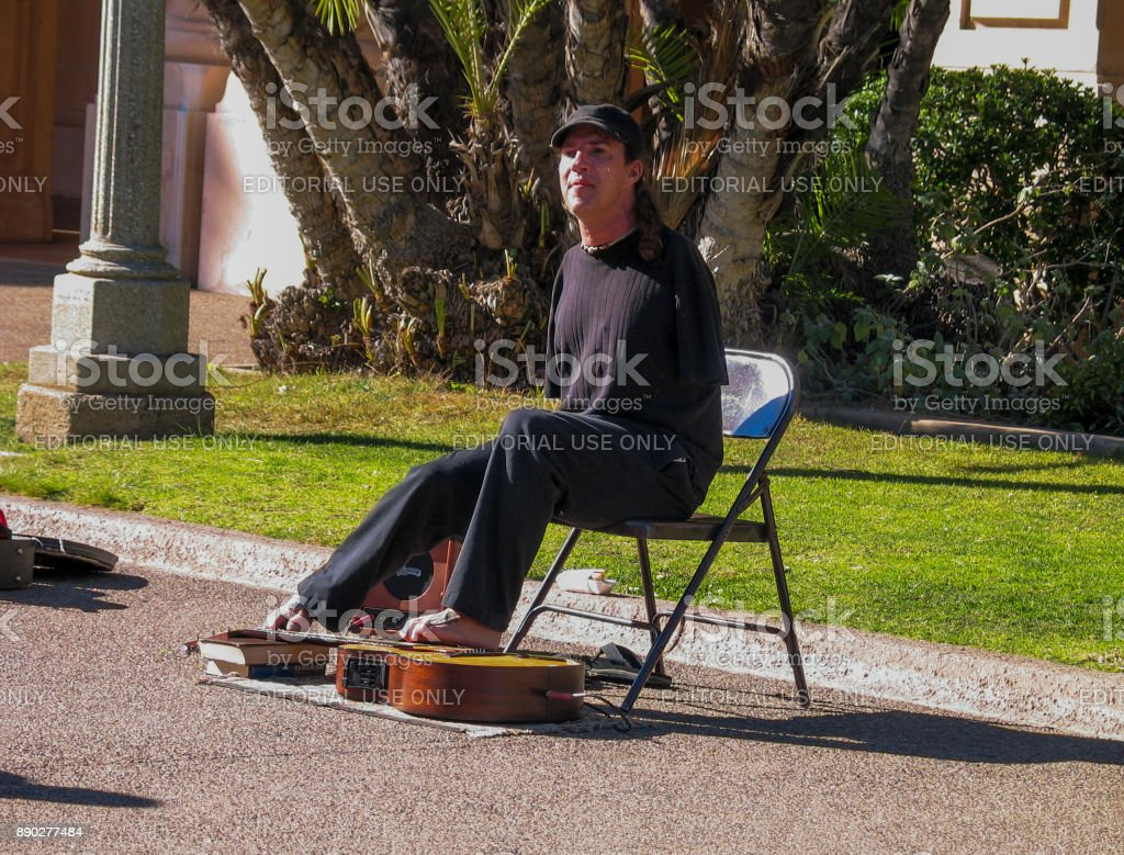 Disabled armless person plays on guitar by his toes in Balboa Park in San Diego, California on March 12, 2007. stock photo