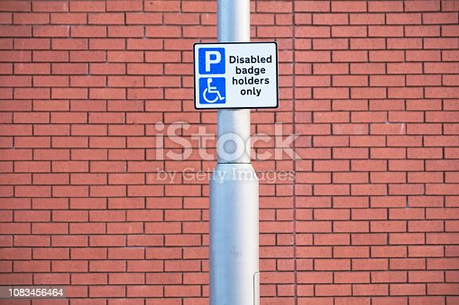 istock Disabled Badge Holders Only at Car Park Sign Post 1083456464