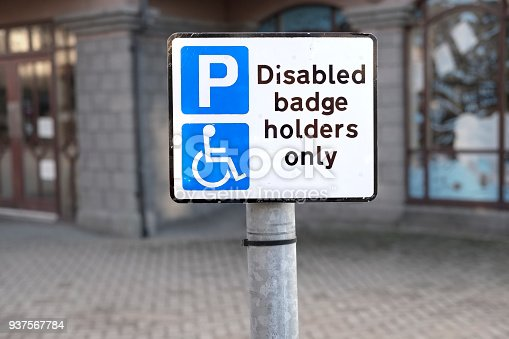 istock Disabled badge holders only sign parking space in car park at shops 937567784