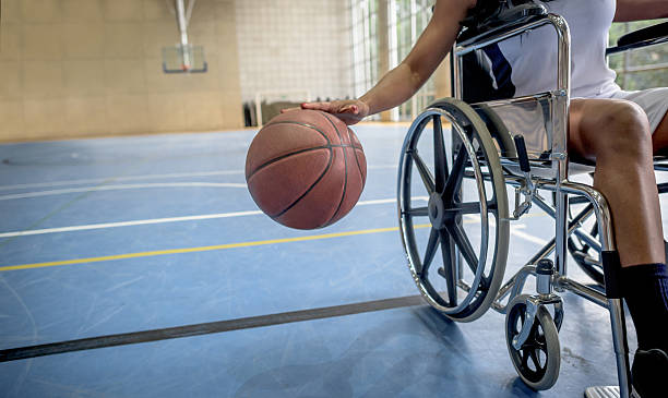 disabled basketball player bouncing the ball - sports en fauteuil roulant photos et images de collection