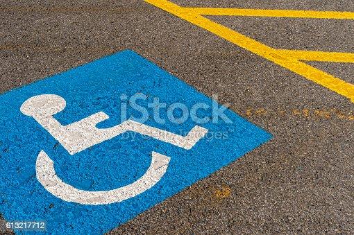 disabled blue parking sign painted on dark asphalt in Canada