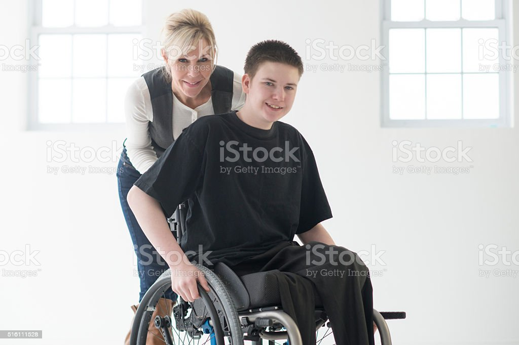 Disabled Boy Getting Help from a Caregiver stock photo