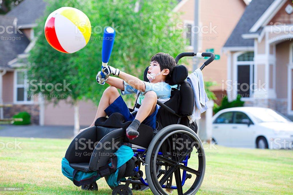 Niño con discapacidad que sobrepasemos bola con el bat en el parque - foto de stock