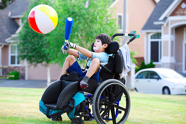 disabled boy hitting ball with bat at park - wheelchair sports stock photos and pictures
