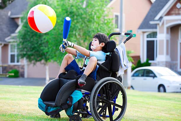 desativado menino atingir bola com um taco no parque - esportes em cadeira de rodas - fotografias e filmes do acervo