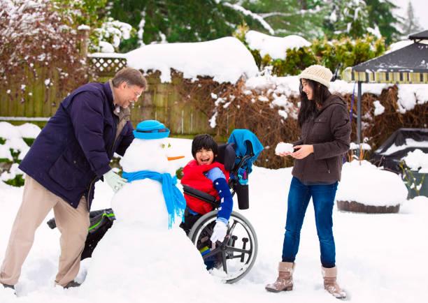 冬の家族と車椅子の建物の雪だるまの障害者の少年 - disabilitycollection ストックフォトと画像