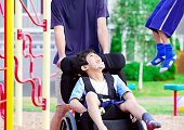istock Disabled boy in wheelchair enjoying watching friends play at park 519974819