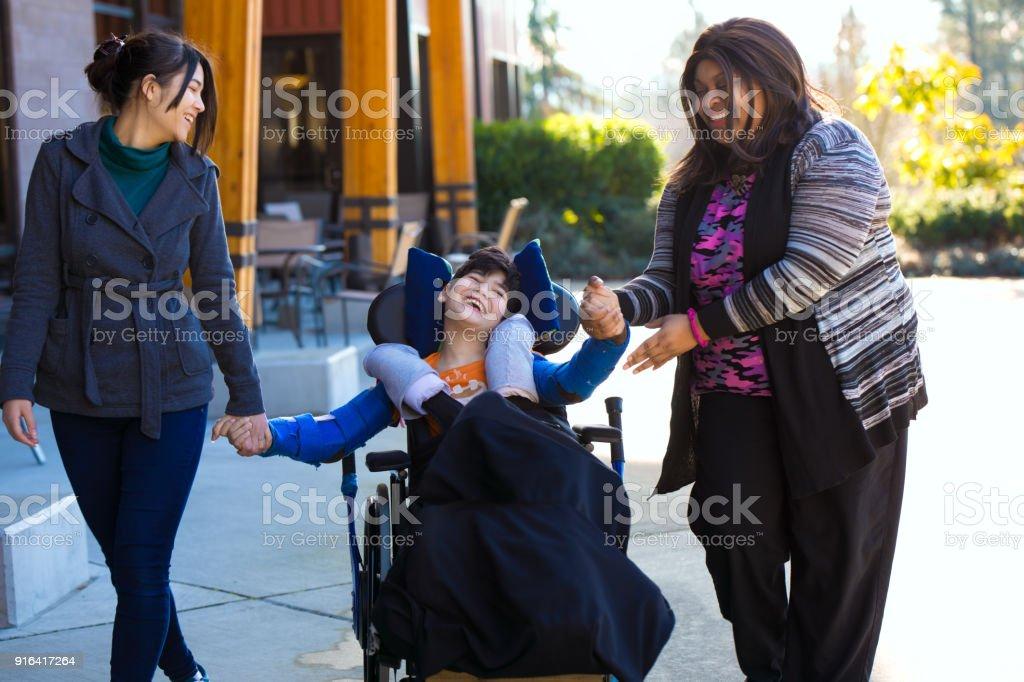 Behinderte junge im Rollstuhl, Hand in Hand mit Betreuern auf Spaziergang – Foto