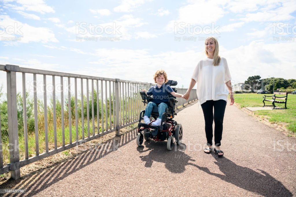 Disabled boy in wheelchair holding mother's hand on path stock photo