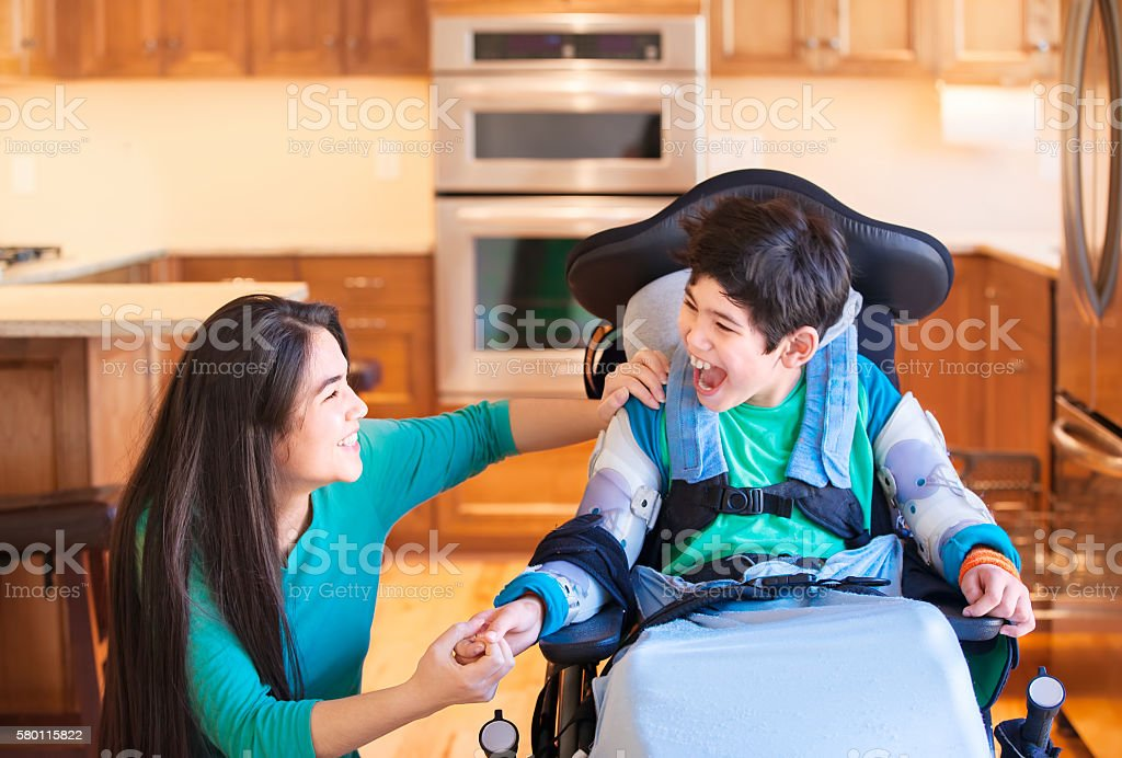 Disabled boy in wheelchair laughing with teen sister in kitchen stock photo