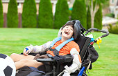 istock Disabled boy in wheelchair playing with soccer ball at park 618969054