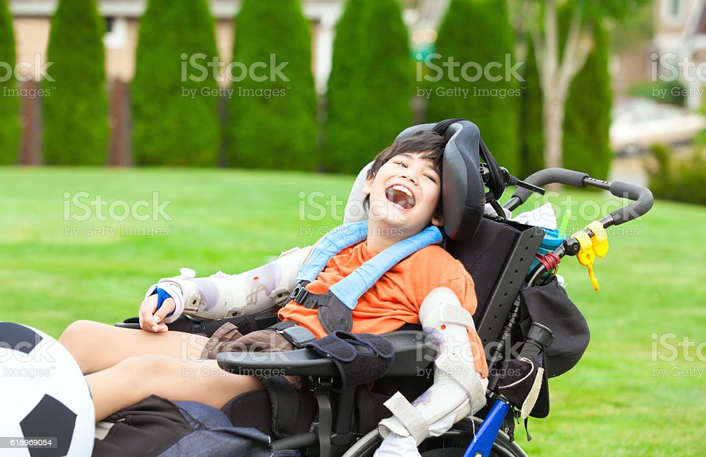 Disabled boy in wheelchair playing with soccer ball at park stock photo