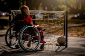 istock Disabled boy playing with sports ball 1273354045
