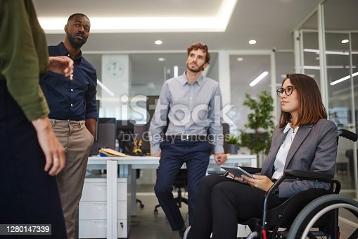 Disabled asian business woman in wheelchair chatting with coworkers in business office holding digital tablet