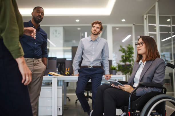 Disabled business woman in wheelchair chatting with coworkers in office stock photo