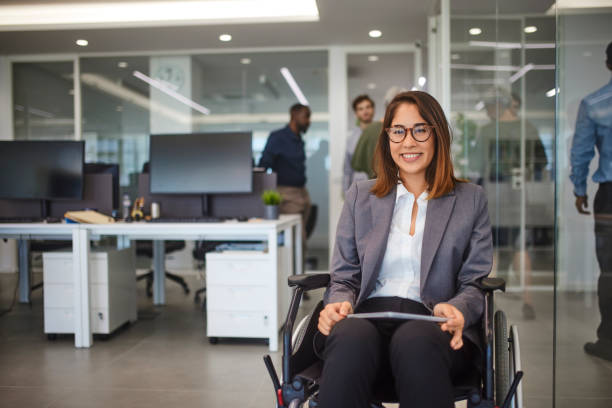 Disabled business woman in wheelchair holding table smiling in office stock photo