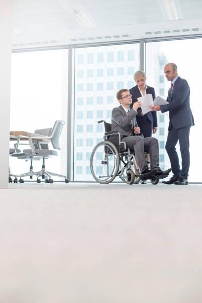 Behinderte Geschäftsleute diskutieren während der Sitzung im Amt mit Kollegen in der Vorstandsetage über Dokumente – Foto