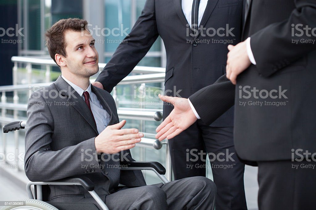 Disabled businessman shaking hand with business partners stock photo