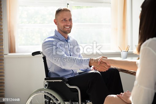 1144373653 istock photo Disabled Businessman Shaking Hand With His Partner 975124448