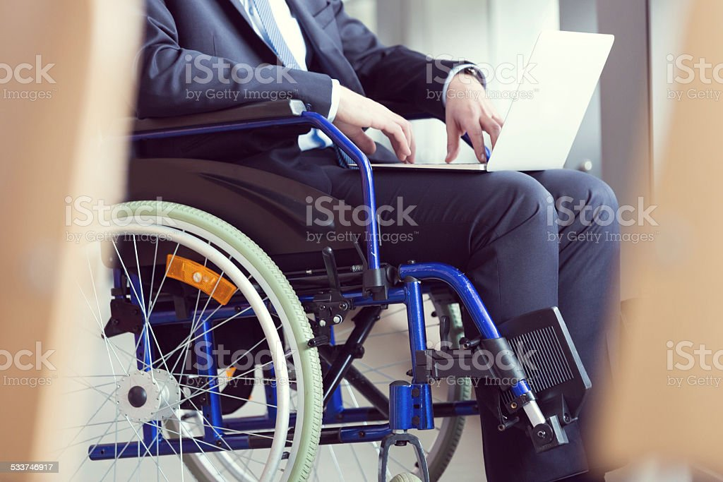 Disabled businessman sitting in a wheelchair Disabled businessman sitting in a wheelchair and using a laptop. 2015 Stock Photo