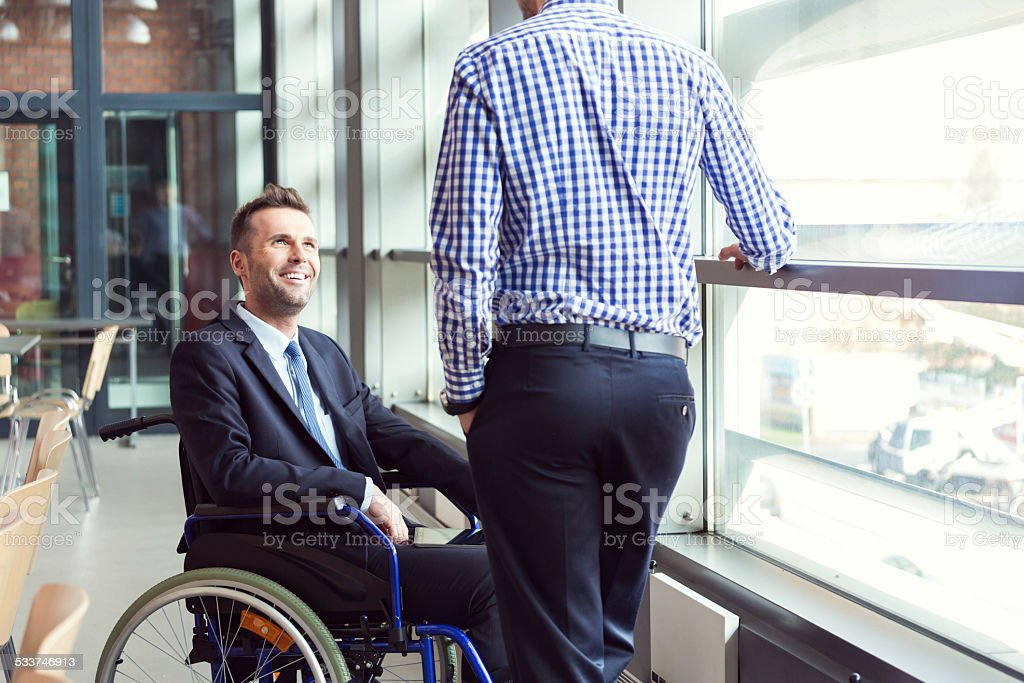 Disabled businessman talking with coworker Disabled businessman sitting in a wheelchair talking with coworker in the office.  2015 Stock Photo