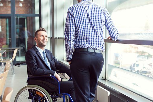 Disabled Businessman Talking With Coworker Stock Photo - Download Image Now